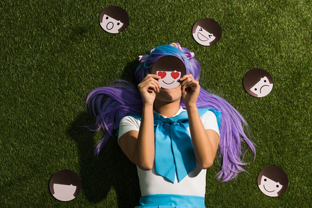 Anime girl in purple wig lying on grass with emoticons