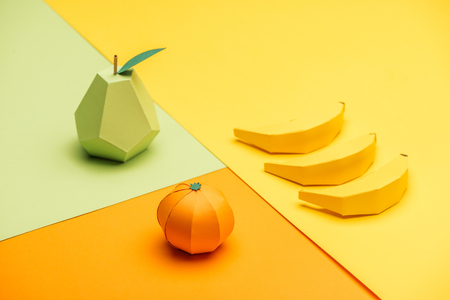 handmade origami pear, bananas and tangerine on colorful paper 스톡 콘텐츠