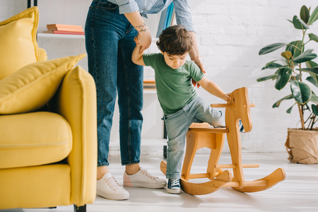cropped view of mother and son with wooden rocking horse