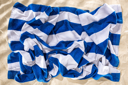 top view of crumpled blue and white striped beach towel on sand