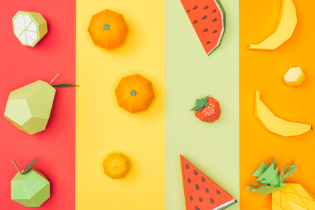 top view of various handmade origami fruits on multicolored paper stripes Stock Photo