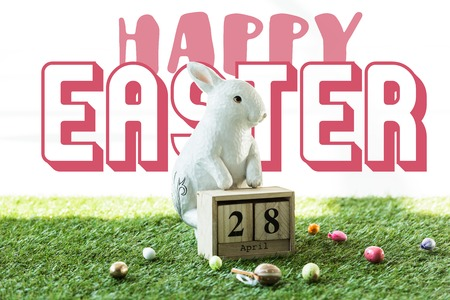 decorative rabbit, wooden calendar with 28 April date, and colorful Easter eggs on green grass with happy Easter lettering Imagens