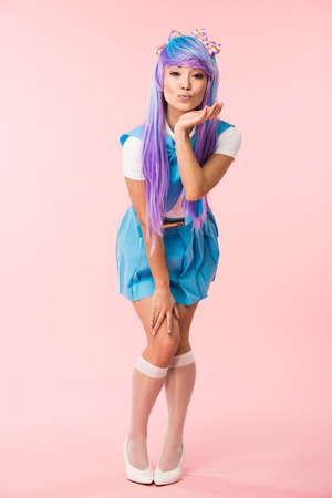 Full length view of asian anime girl in purple wig posing with kissing face expression on pink