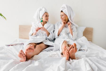 selektywne skupienie bosych dziewczyn w kolczykach, szlafrokach i ręcznikach na głowach leżących w łóżku i patrzących na siebie