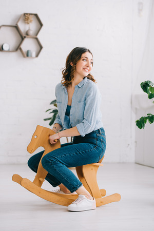 Joyful woman in jeans sitting on rocking horse and looking away Stock Photo