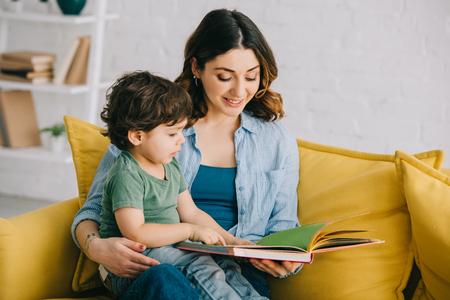 Mamá e hijo sentados en el sofá amarillo y libro de lectura