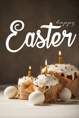 Traditional tasty Easter cakes with burning candles and white chicken eggs on brown background with happy easter lettering