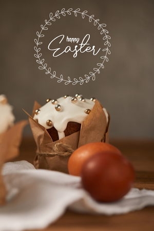 selective focus of traditional Easter cake in craft paper and chicken eggs on napkin with happy easter lettering in circle above