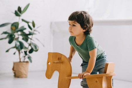 cute child with wooden rocking horse in living room