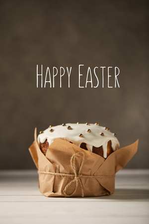 traditional decorated Easter cake in craft paper on white table with happy easter lettering on brown background