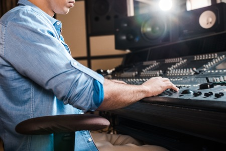 partial view of mixed race sound producer working at mixing console in recording studio Stock fotó