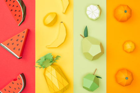 top view of various handmade origami fruits on multicolored paper stripes