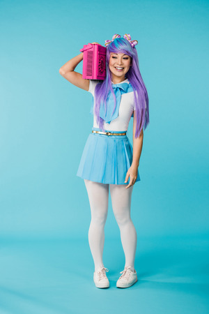 Full length view of asian anime girl holding pink boombox on blue