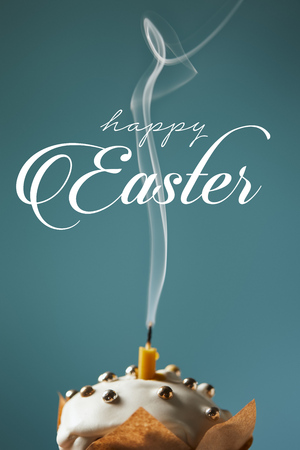 traditional Easter cake with fireless candle and smoke on blue background with happy easter lettering Imagens
