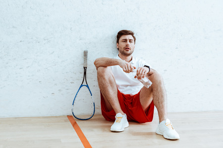 Tired squash player sitting on floor and opening bottle of water