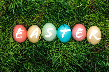 top view of painted multicolored eggs with Easter word on green grass