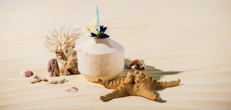 Coconut cocktail, starfish, coral and sea stones on beach