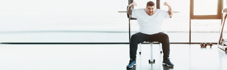 Panoramic shot of overweight tattooed man sitting on bench and showing muscles at gym