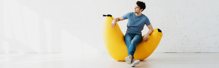 Panoramic shot of happy man sitting on yellow bean bag chair at home