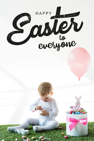 Cute baby sitting near box with colorful quail eggs, toy rabbit and air balloon on white background with happy Easter to everyone lettering Imagens