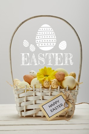 wicker basket with colorful eggs, yellow gerbera flower, greeting card and Easter lettering on grey background
