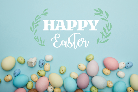 top view of painted multicolored eggs scattered and decorative bunny on blue background with happy Easter lettering Фото со стока