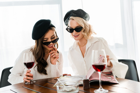 brunette and blonde smiling women in black berets and sunglasses drinking red wine and reading magazine