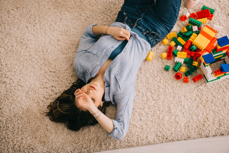 overheaf view of tired woman lying on carpet with colorful toy blocks 写真素材