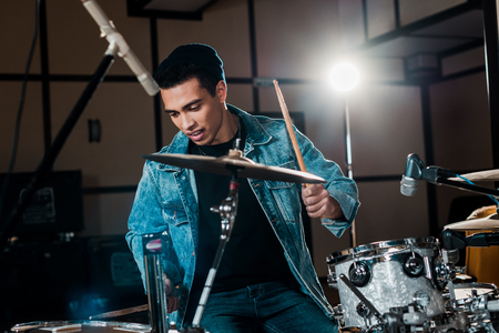 handsome, inspired mixed race musician playing drums in recording studio Stock fotó