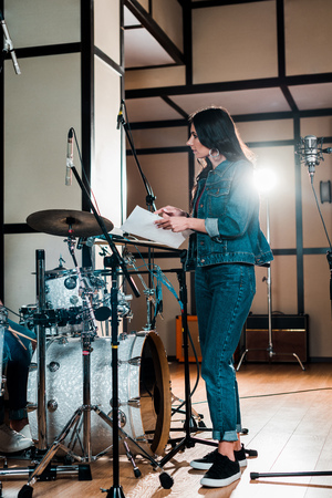 attractive singer standing near microphone and holding paper with text in recording studio Stok Fotoğraf