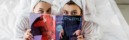 panoramic shot of women with towels on heads hiding behind magazine in bed