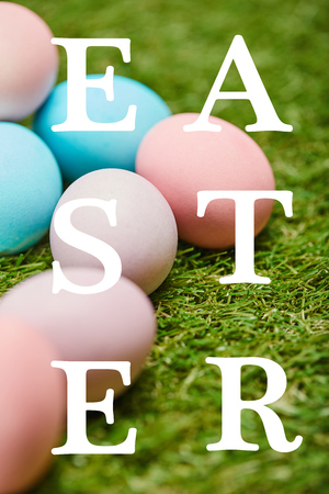 pile of multicolored painted chicken eggs with Easter lettering on green grass