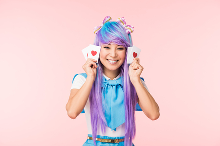 Happy asian anime girl in purple wig holding cards with hearts isolated on pink