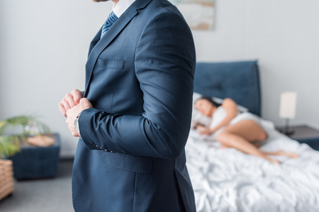 cropped view of man touching formal wear near sleeping woman 版權商用圖片