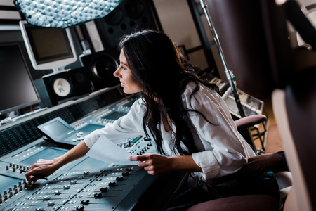 smiling sound producer working in recording studio at mixing console Stock Photo