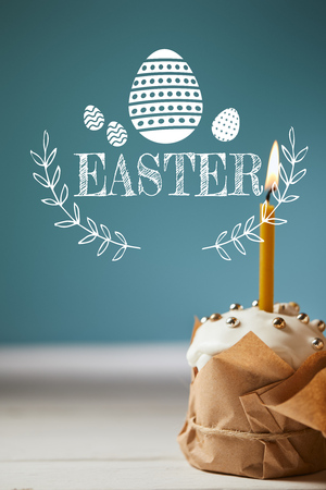 traditional Easter cake with burning candle on blue background with easter lettering