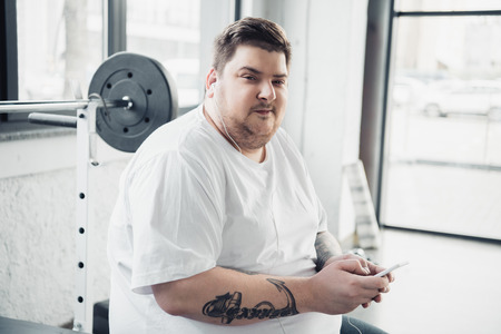 overweight man in earphones sitting on bench, looking at camera and using smartphone at gym