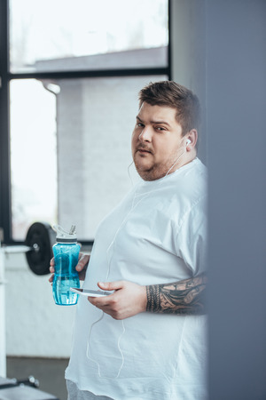 overweight tattooed man holding sport bottle, looking at camera and using smartphone at gym