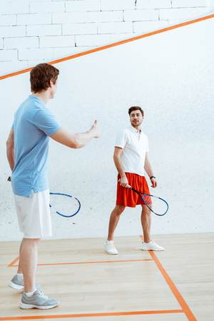 Full length view of squash players looking at each other with thumb up