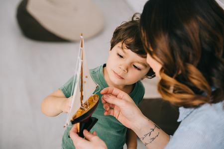 母亲和小儿子播种的看法有玩具船的