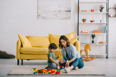 Mother and son playing with lego on carpet in living room