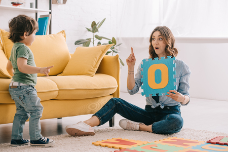 emotional mother showing idea sign while learning letters with son