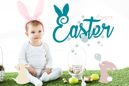cute baby in bunny ears headband sitting near painted chicken and quail eggs and Easter illustration Stock Photo