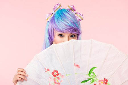 Asian anime girl in wig holding paper umbrella isolated on pink background