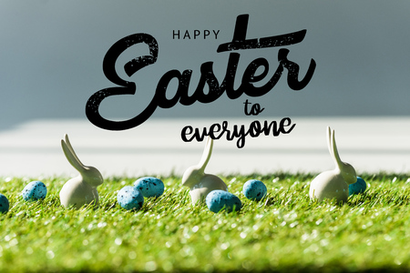 decorative rabbits on green grass near blue quail eggs with happy Easter to everyone illustration