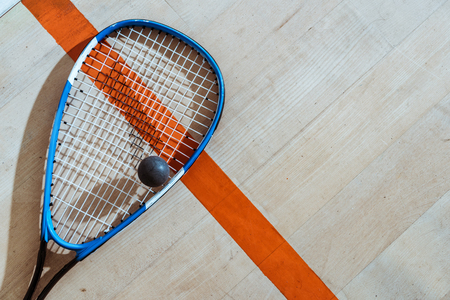 Top view of squash racket and ball on wooden surface 스톡 콘텐츠