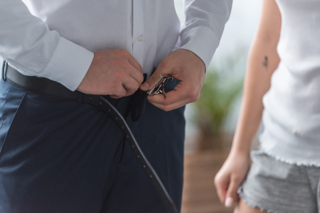 Cropped view of man wearing pants and touching belt while standing with woman at home