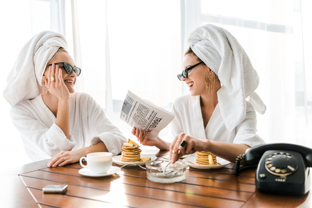 stylish happy women in bathrobes, sunglasses and jewelry with towels on heads smoking cigarette, laughing and reading newspaper at morning Banque d'images