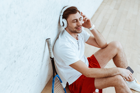 Smiling squash player sitting on floor and listening music in headphones with closed eyes Reklamní fotografie