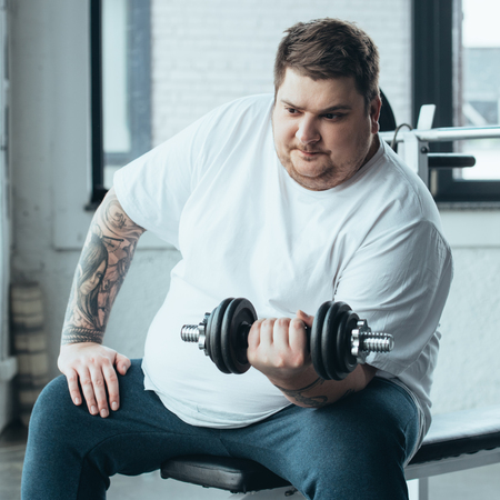 Overweight tattooed man sitting and exercising with dumbbell at sports center 版權商用圖片